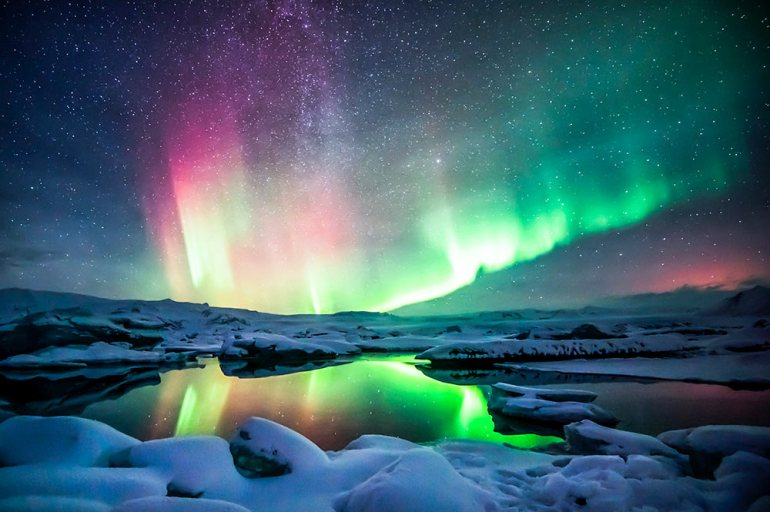 northern lights over snowy lagoon