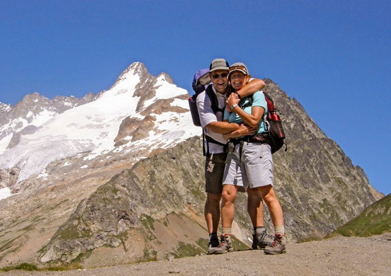 two hikers hugging on the tour du mont blac trail with the mountain behind them