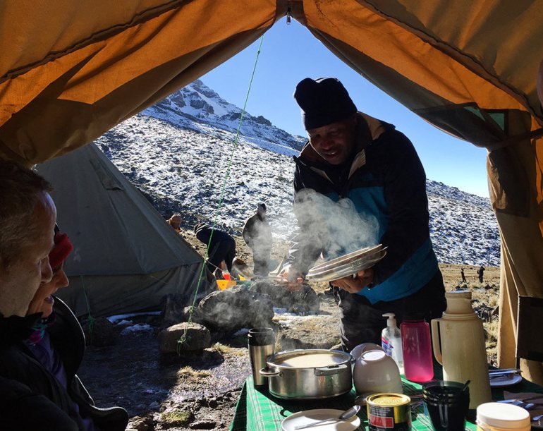 man serving warm food in tent in kilimanjaro