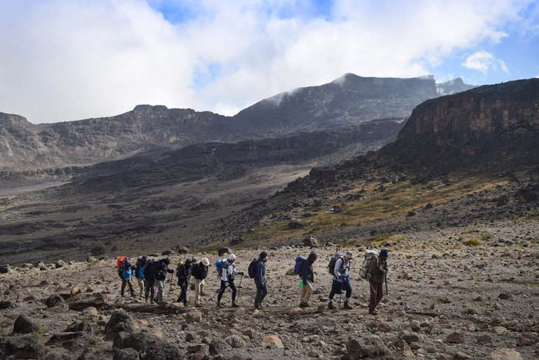 hiker walking up the mountain of kilimanjaro
