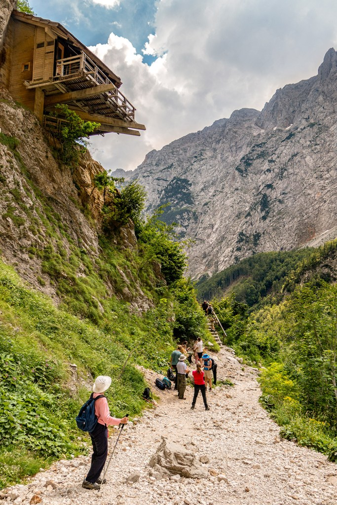 hikers on path near house on cliff in Slovenia