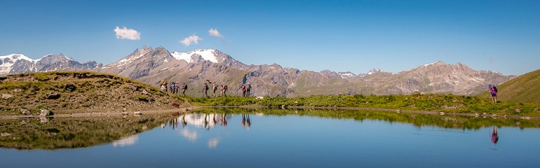 hikers near a lake on the haute route