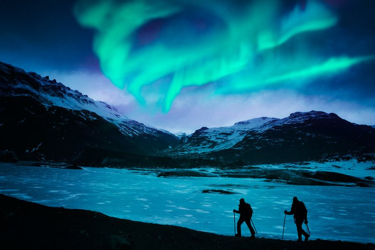 northern lights over snow shoe hikers