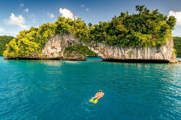 snorkeling near an arch in palau rock islands