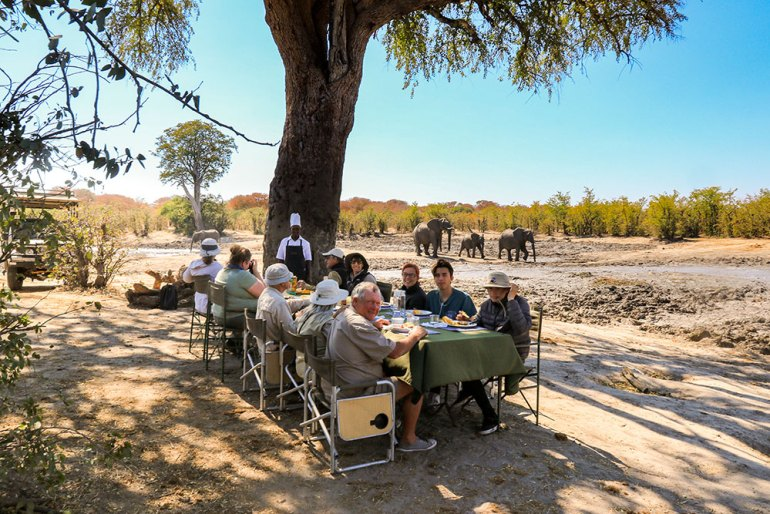 group eating meal under tree in zimbabwe