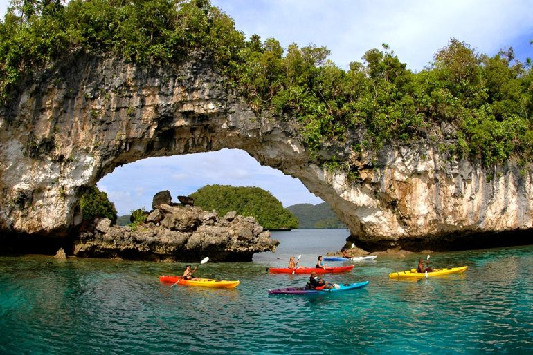 kayakers near natural arch in palau