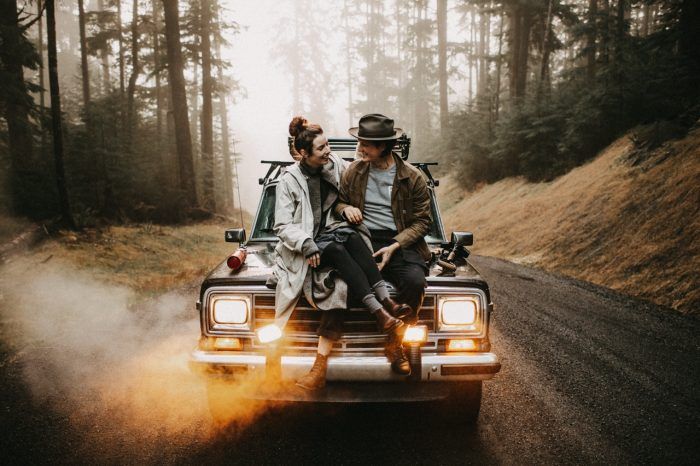 couple sitting on a car with headlights on