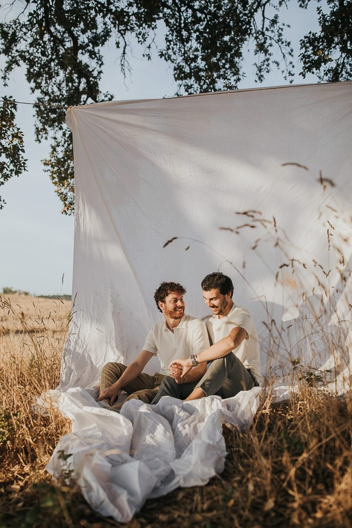 same sex couple posed on sheet in a field
