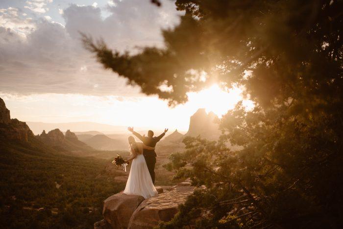 exuberant couple on mountain peak at dusk
