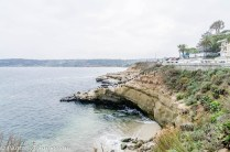 The rocky shoreline features a scenic walkway.