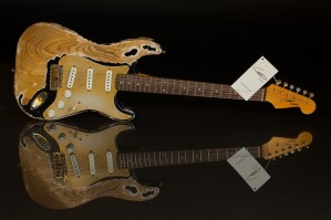 Heavily-relic'ed guitar against black background with glass for full reflection