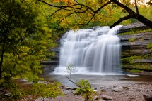 Long exposure of large adirondack waterfall framed by tree branch