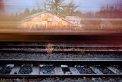 Long exposure of yellow train car moving over tracks and in front of house
