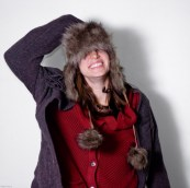 Girl in smiling while wearing sweater and fur hat