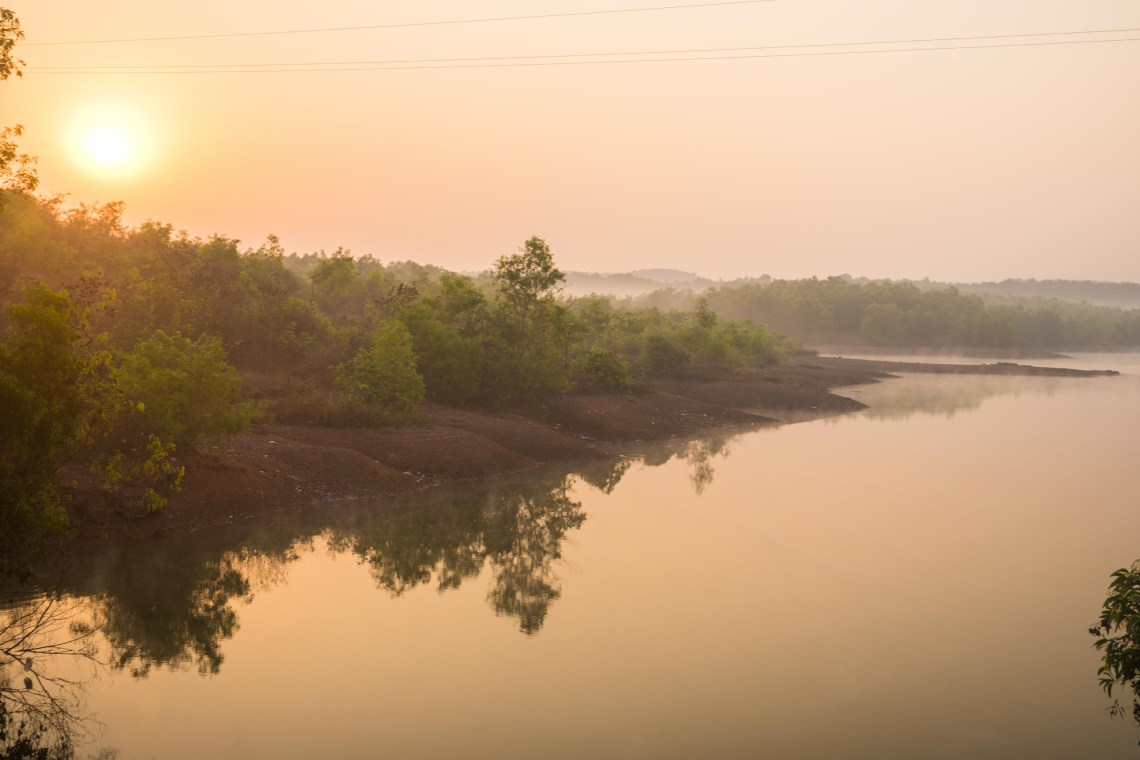 A river in India reflecting the beach and the rising sun in a misty morning atmosphere