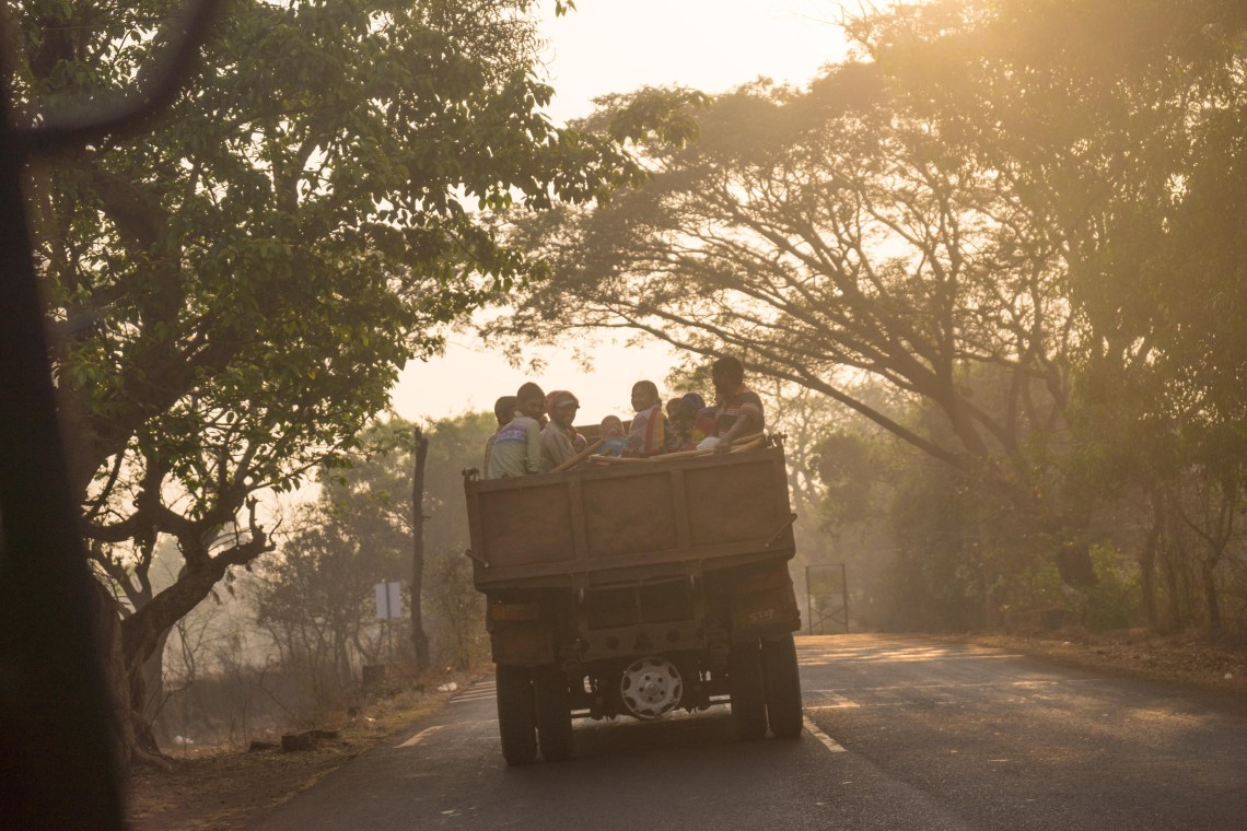 A bunch of people traveling on top of a truck as seen often in rural areas of India.