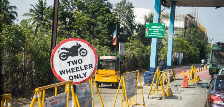 Sign displaying that just two-wheel vehicles are allowed on a street with a three-wheel rickshaw in the background