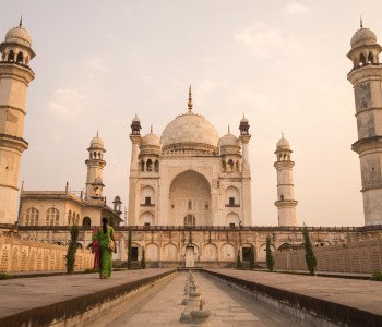 A woman dressed in typical Indian garments walking down a way towards the Bibi ka Maqbara, a Taj Mahal like building in Aurangabad