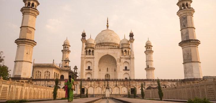 A woman dressed in typical Indian garments walking down a way towards the Bibi ka Maqbara, a Taj Mahal like building in Aurangabad