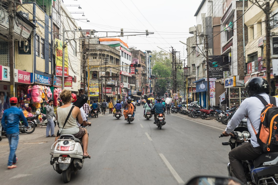 Photodyssee author Flo on a scooter in the city traffic of Indore