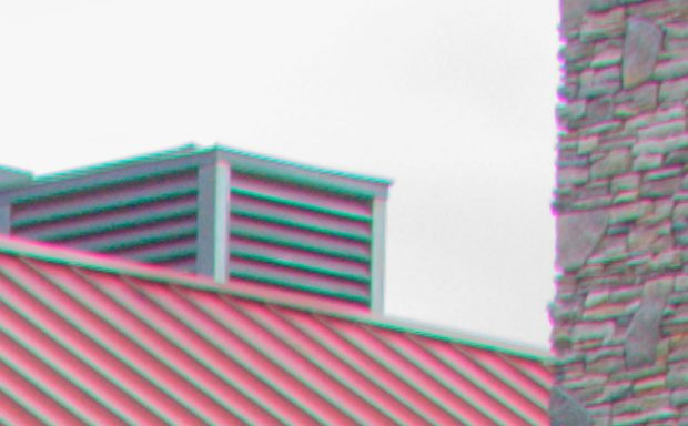 This is a crop from the brightest frame used to make the HDR image above. Zoomed in to 300% you can see the green bands on the ridges of the roof, the green halo on the vent, and even the purple halo on the chimney.