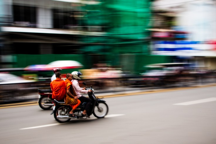 A couple of monks hopping a ride atop a motorbike in Phnom Penh, Camobia