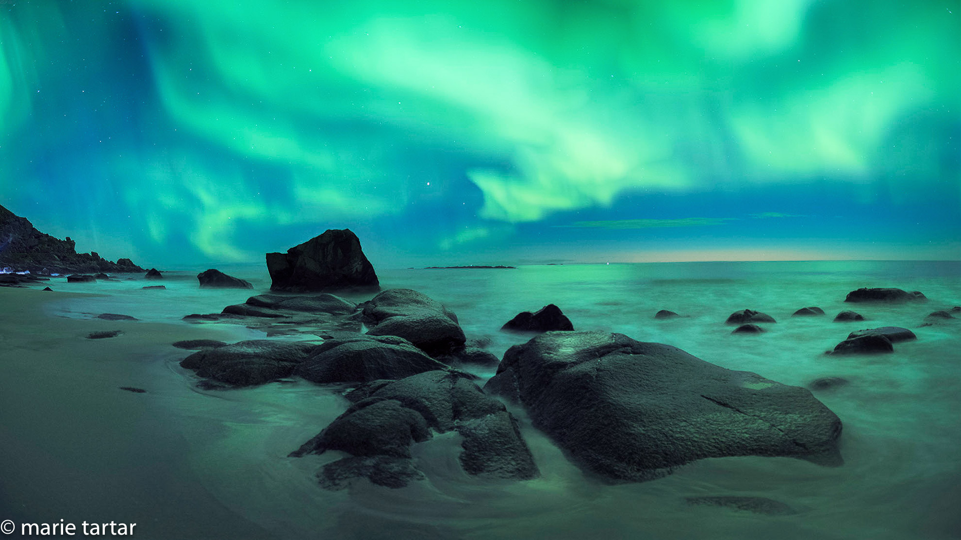 Northern Lights panorama on a boulder beach in Lofoten in northern Norway