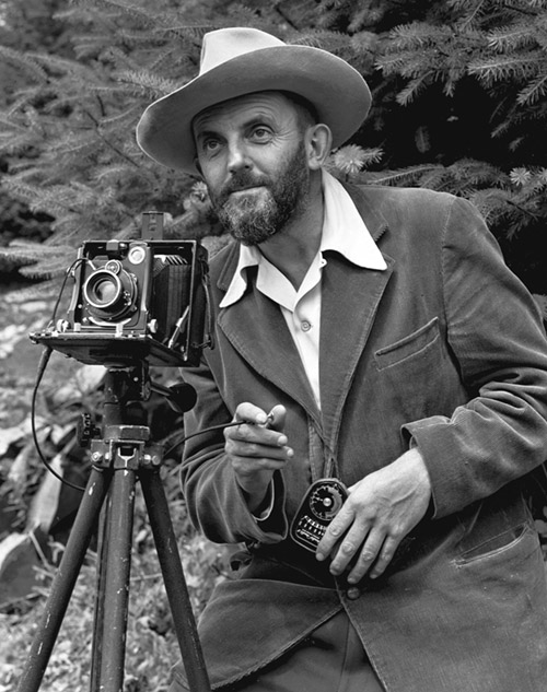Ansel Adams with a field camera and lightmeter.