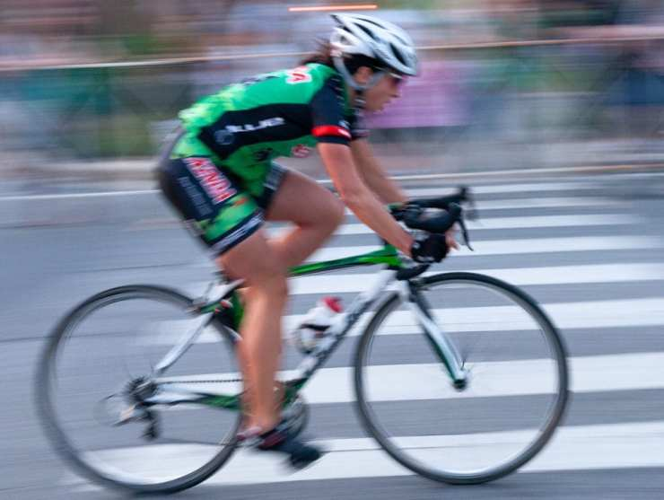 Panning with the action blurs the background and reveals a sharper and fast moving bicyclist.