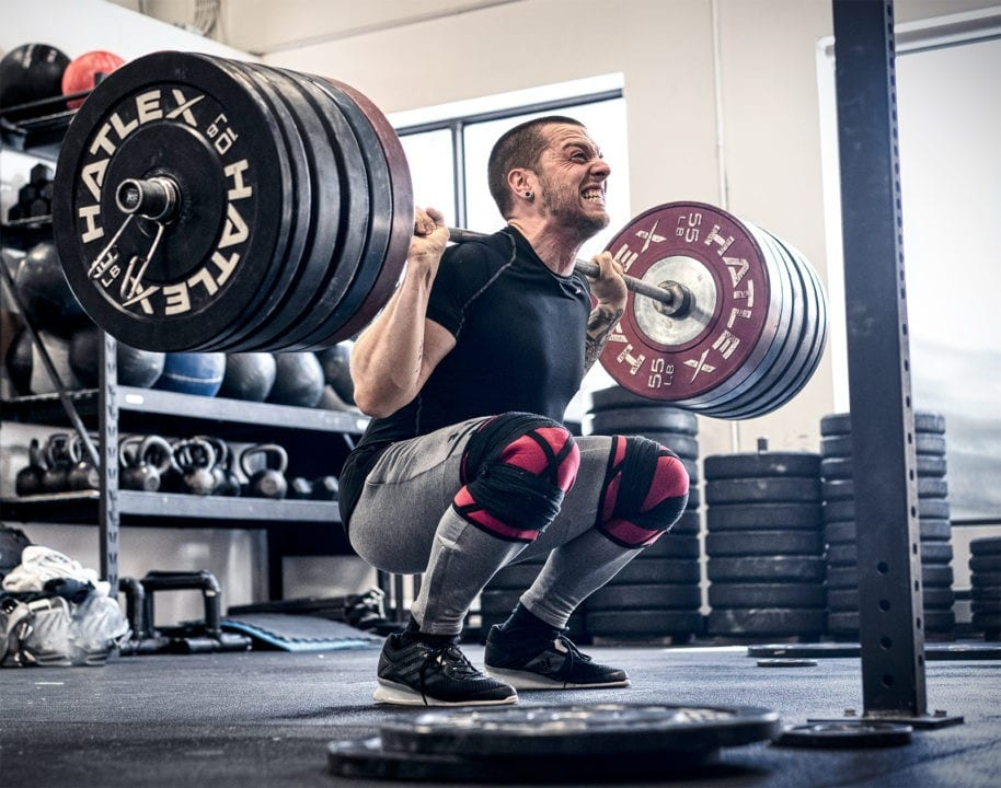 Olympic weightlifter Maxim Lebrun does a heavy squat ass to the grass.