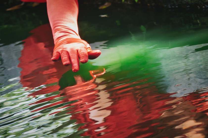 lady with red glove touching water