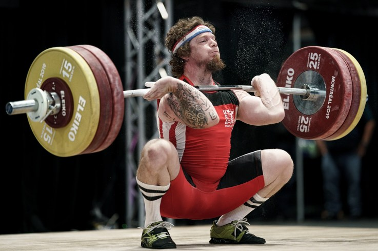 International weightlifter athlete Chad Vaughn doing a squat clean at the 2019 World Masters Weightlifting sports event