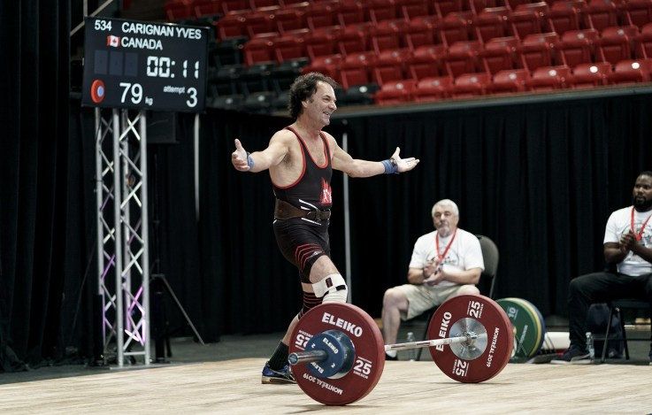 International Olympic Weightlifter sports on the platform smiles to the crown the barbell in front of him
