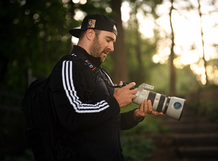 Male photographer with Sony camera and lens.