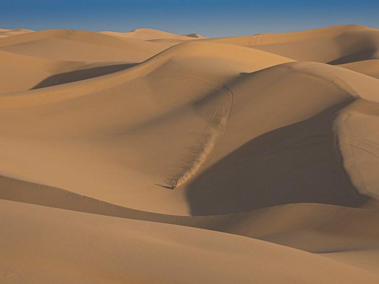 dirt bike racing across the sand dunes Imperial Dunes, CA