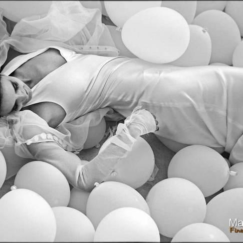 Mariée allongée dans la piscine au milieu des ballons