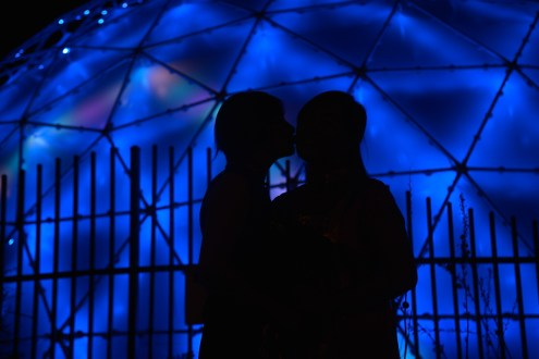 Photographers of Las Vegas - Wedding Photography - wedding couple shadows couple kiss with neon dome behind at container park
