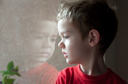 Photographers of Las Vegas - Portrait Photography - window refelection boy in red shirt