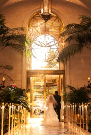 Photographers of Las Vegas - Wedding Photography - couple walking out with sun through the glass