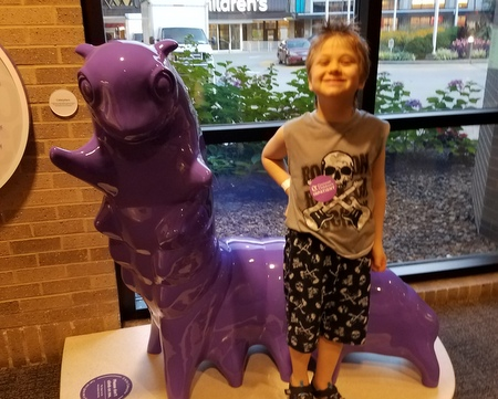 Young Boy standing next to a Purple Caterpillar Statue