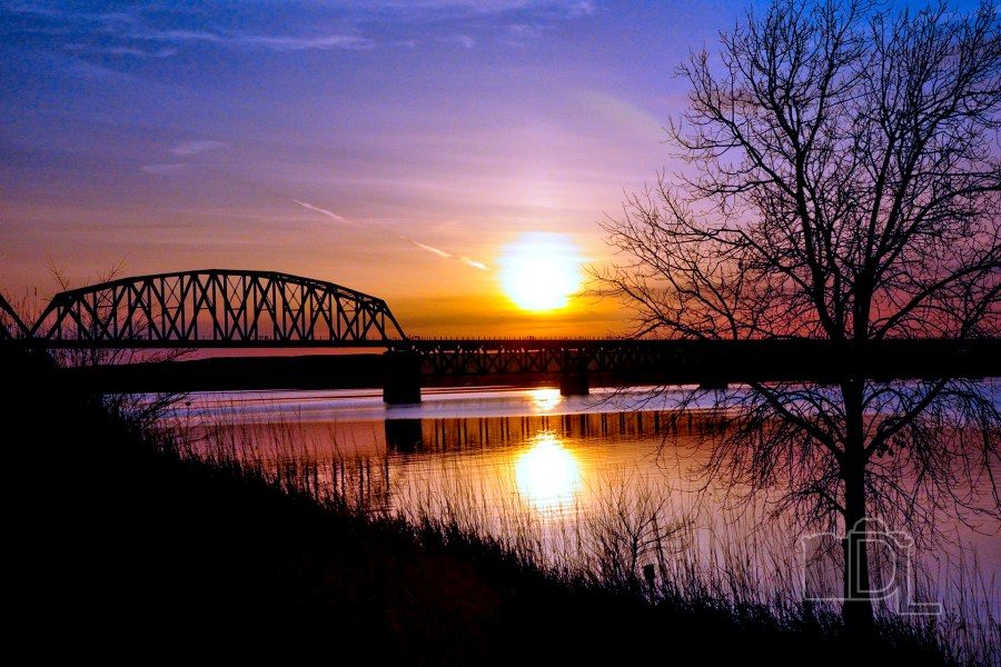 The sun sets over a railroad bridge spanning the Missouri River in Chamberlain, South Dakota.
