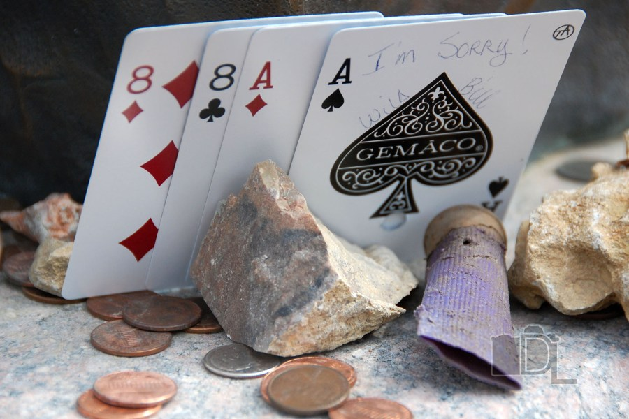 A poker hand of Aces and Eights, a spent shell and some change sits at the foot of the grave site of Wild Bill Hickok in Deadwood, South Dakota.