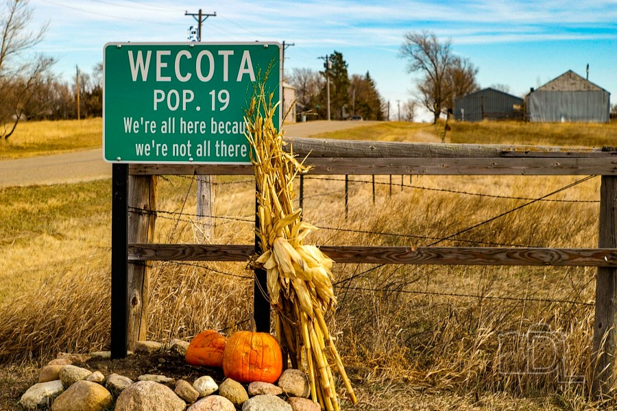 A humorous road sign pokes fun at the tiny population of the town of Wecota, South Dakota.