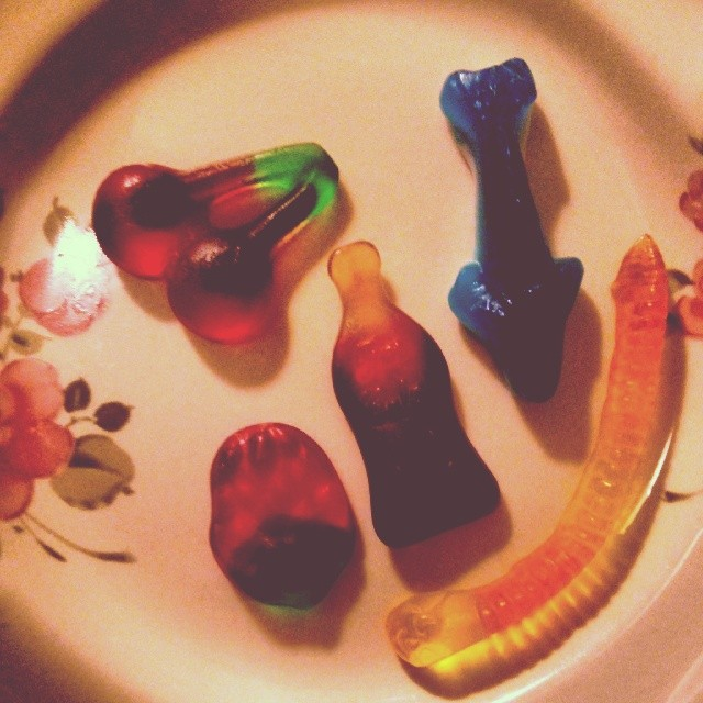 a photo of a gummy cherry, gummy strawberry, gummy rootbeer, gummy shark and gummy worm on a plate