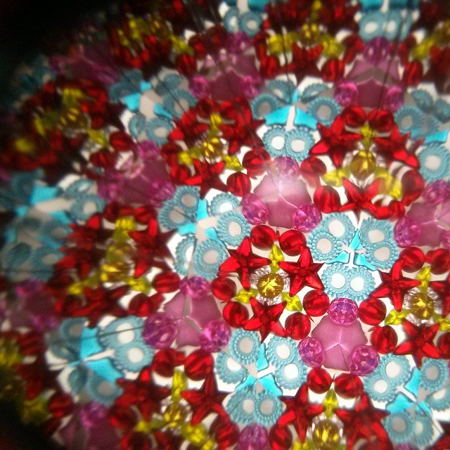 a photo of the inside of a kaleidoscope, it features blue, pink, red and yellow crystals