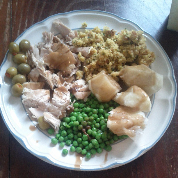 a photo of a plate of olives, turkey, peas, potatoes and stuffing covered in gravy