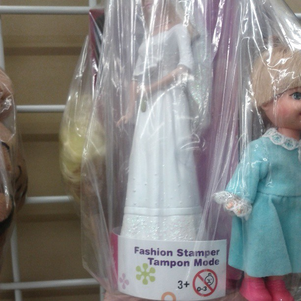 "a photo of a barbie doll labelled ""fashion stamper tampon mode"""