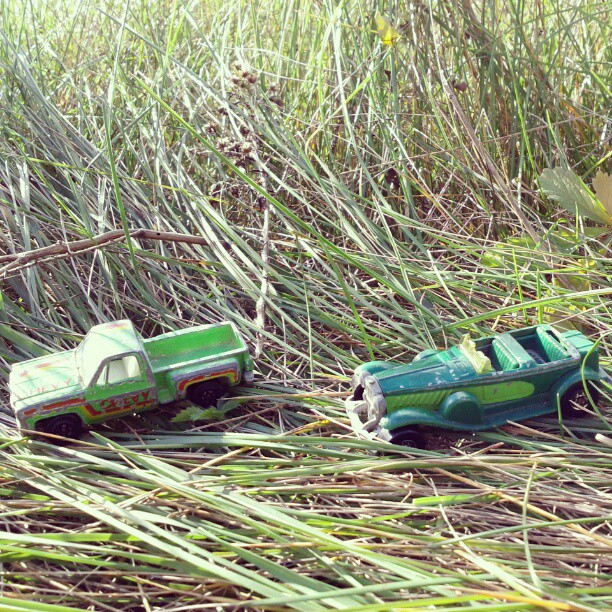 a photo of two green toy cars in some grass