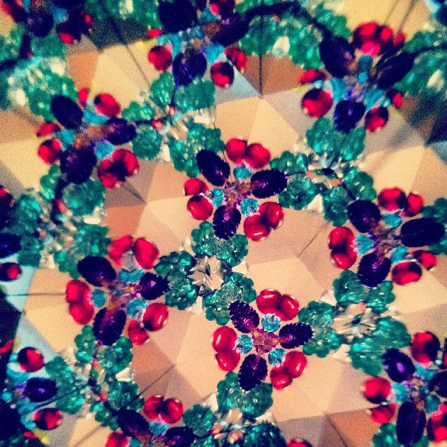 a photo of the inside of a kaleidoscope, includes green red and purple crystals