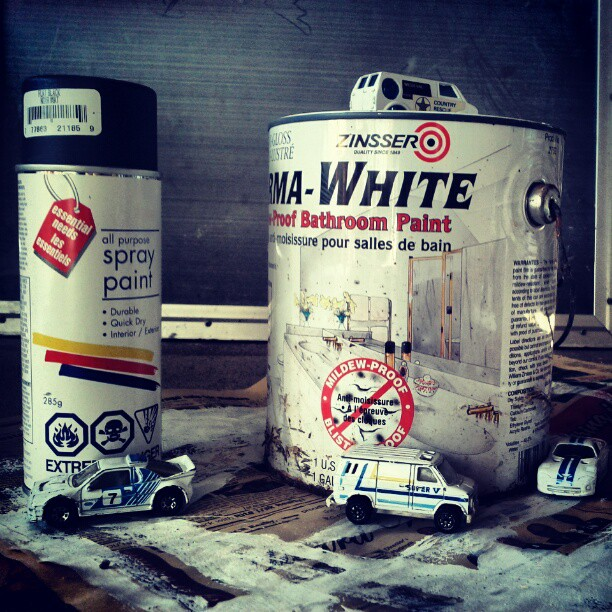 a photo of white toy cars and some white cans of paint